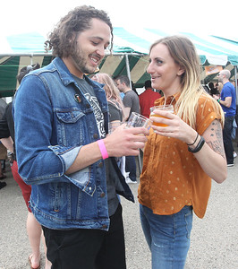 Candace H. Johnson-For Shaw Media Ryan Jackson, of Grayslake and Regina Marturano, of Wheeling enjoy drinking their beers together during the 6th Annual Grayslake Craft Beer Festival in downtown Grayslake.(6/2/18)