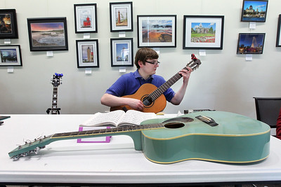 Candace H. Johnson-For Shaw Media Ian Lutz, of Buffalo Grove, a page at the library, plays classical music on his guitar at the guitar table during the Musical Petting Zoo event at the Wauconda Area Library.Lutz has been playing guitar for eighteen years.(6/4/18)