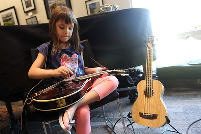 Candace H. Johnson-For Shaw Media Angelica Kadukov, 5, of Wauconda plays the mandolin using a pick during the Musical Petting Zoo event at the Wauconda Area Library.(6/4/18)