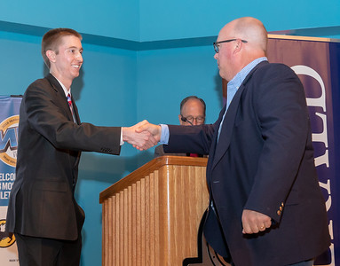 Prairie Ridge head football coach Chris Schremp is congratulated by Sean Hammond (left) after being selected Coach of the Year at the 2018 Northwest Herald's Most Valuable Athlete Awards Thursday, June 7, 2018 at McHenry County College in Crystal Lake. KKoontz – For Shaw Media