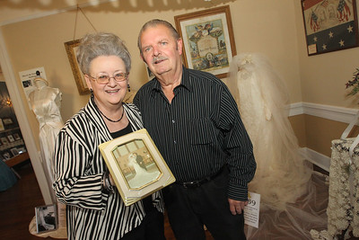 "Candace H. Johnson-For Shaw Media JoAnn Pock, of Arlington Heights stands close to her husband, Jack, as she holds up their wedding picture from August 23rd, 1969 with her wedding dress on the right behind them on display at the Wauconda Area ""Weddings and Gowns Through the Years"" exhibit at the Andrew C. Cook House on Main Street in Wauconda. The Pock's will be married forty-nine years this year.(6/9/18)"