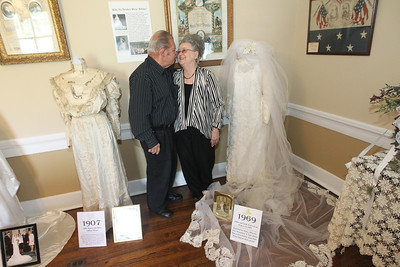"Candace H. Johnson-For Shaw Media Jack and JoAnn Pock, of Arlington Heights share a tender moment next to her 1969 wedding dress (on the right) on display at the Wauconda Area ""Weddings and Gowns Through the Years"" exhibit at the Andrew Cook House on Main Street in Wauconda. The Pock's will celebrate their forty-ninth wedding anniversary this year.(6/9/18)"