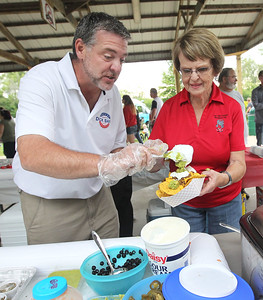 Candace H. Johnson-For Shaw Media Dick Barr, of Round Lake Beach helps Betty Burns, of Lake Villa make nachos to sell for the Lake Villa Township Republican Club fundraiser during the Village of Lake Villa's Celebration of Summer at Lehmann Park.(6/9/18)