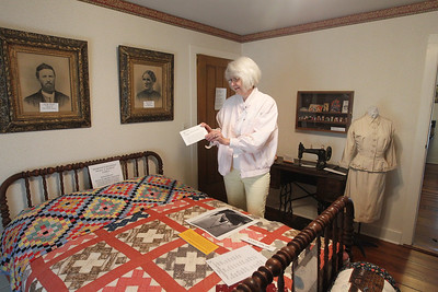 Candace H. Johnson-For Shaw Media Trish Wendt, of Gurnee reads the information card telling the story of the signature quilt, made in 1886, that is draped over a bed in one of the bedrooms at the Mother Rudd House on Old Grand Avenue in Gurnee. (6/11/18)
