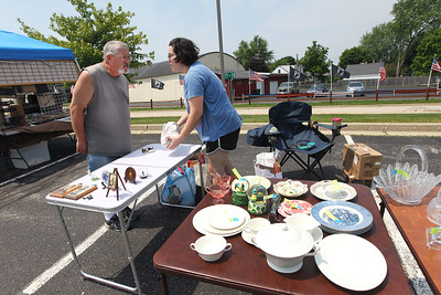 Candace H. Johnson-For Shaw Media Barry O'Connor talks with his daughter, Denise Vick, both of Lindenhurst, as she puts out their vintage antiques to sell on tables during the 3rd Saturday Market at the Lake Villa Train Station parking lot. The market runs on the 3rd Saturday, June through September, and features vendors, arts & crafts and individuals selling their treasures. The event was presented by the Lake Villa Historical Society.(6/16/18)