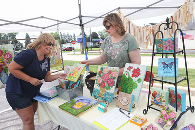 Candace H. Johnson-For Shaw Media Jamie McDonald, of Lake Villa looks to buy a mixed media flower painting from Jennifer Evans, with the Periwinkle Art Studio, during the 3rd Saturday Market at the Lake Villa Train Station parking lot. The market runs on the 3rd Saturday, June through September, and features vendors, arts & crafts and individuals selling their treasures. The event is presented by the Lake Villa Historical Society.(6/16/18)