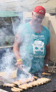 Candace H. Johnson-For Shaw Media Mayor Donny Schmit cooks brats on the grill during the Fox Lake Volunteer Fire Department's 60th annual Fireman's Festival on Washington Street in Fox Lake.
