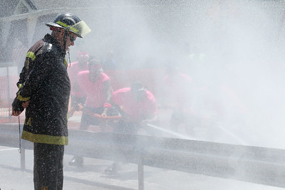 Candace H. Johnson-For Shaw Media Lt. Greg Phillips with the Lake Villa Fire District gets wet as he helps monitor the water fight between Heather's Hair and the Gutter Guys during the Fox Lake Volunteer Fire Department's 60th annual Fireman's Festival on Washington Street in Fox Lake.(6/24/18)