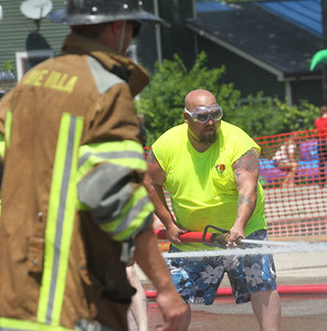 Candace H. Johnson-For Shaw Media Jack McNamara with Fox Valley Fire & Safety holds the fire hose as his team competes against the Gutter Guys during the Fox Lake Volunteer Fire Department's 60th annual Fireman's Festival on Washington Street in Fox Lake.(6/26/18)