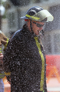 Candace H. Johnson-For Shaw Media Lt. Greg Phillips with the Lake Villa Fire District gets wet as he helps monitor the water fight between Heather's Hair #1 and Top and Drop during the Fox Lake Volunteer Fire Department's 60th annual Fireman's Festival on Washington Street in Fox Lake.(6/24/18)