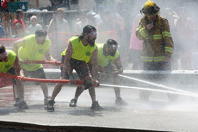 Candace H. Johnson-For Shaw Media The Gutter Guys team takes control using fire hoses to push an aluminum keg as they compete against the Heather's Hair #1 team during the Fox Lake Volunteer Fire Department's 60th annual Fireman's Festival on Washington Street in Fox Lake.(6/24/18)