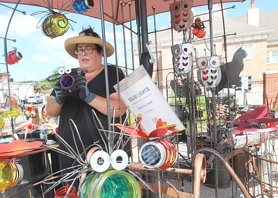 Candace H. Johnson-For Shaw Media Rachel Haynes, of Galesburg, with Stray Cat Art puts together one of her handmade firefly solar lights during the 23rd Annual Grayslake Arts Festival & Wine Tasting on Whitney Street in Grayslake.(6/23/18)