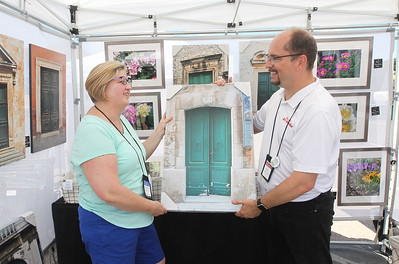 Candace H. Johnson-For Shaw Media Christine Oleson, of Grayslake gets some help from her husband, Tom Perkowitz, showing one of her framed photographs on display during the 23rd Annual Grayslake Arts Festival & Wine Tasting on Whitney Street in Grayslake.(6/23/18)