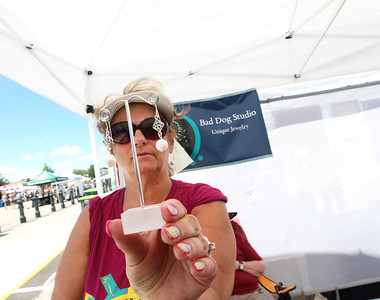 Candace H. Johnson-For Shaw Media Linda Wegge, of Grayslake looks at some earrings from the Bad Dog Studio for sale during the 23rd Annual Grayslake Arts Festival & Wine Tasting on Whitney Street in Grayslake.(6/23/18)