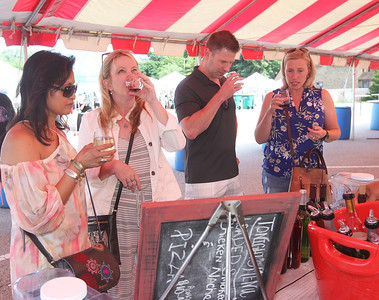 Candace H. Johnson-For Shaw Media Marly Subido, of Lake Villa, Lynne Monroe, of Lindenhurst and Dave and Christy Peterson, of Lake Villa sample wines from Irene's Vineyard, of Oblong, during the 23rd Annual Grayslake Arts Festival & Wine Tasting on Whitney Street in Grayslake.(6/23/18)