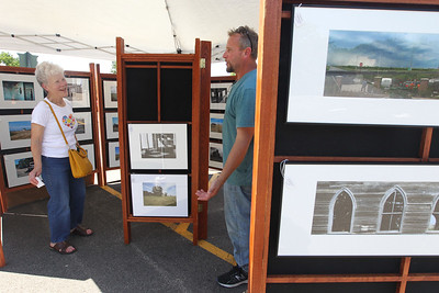 Candace H. Johnson-For Shaw Media Helen Fandrei, of Grayslake talks with Dwight Lohman, of Belvidere, about his rural American photographs on display during the 23rd Annual Grayslake Arts Festival & Wine Tasting on Whitney Street in Grayslake.(6/23/18)