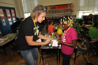 Candace H. Johnson-For Shaw Media Dawn Buckus, of Beach Park helps Asha Sabree, 8, of Waukegan build a car using bottle tops for wheels and moves with a balloon during the iBIO Institute EDUCATE Center's third annual STEMgirls Summer Camp at the Andrew Cooke Magnet Elementary School in Waukegan. (6/20/18)