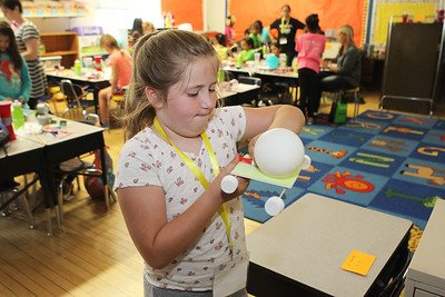 Candace H. Johnson-For Shaw Media Cecilia May, 9, of Waukegan works on attaching a balloon to a car she had made during the iBIO Institute EDUCATE Center's third annual STEMgirls Summer Camp at the Andrew Cooke Magnet Elementary School in Waukegan.The air from the balloon will push the car. (6/20/18)