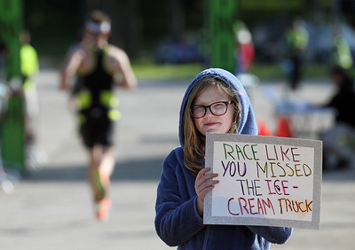 Candace H. Johnson-For Shaw Media Danielle Murphy, 11, of Fox Lake holds up a sign to inspire runners as they come in to the finish line as she waits to see her mother, Lynnette, compete during the Fox Lake Duathlon at Lakefront Park in Fox Lake. The course included a 1-mile run, biking 12.5 miles and then finishing up with a 3.1 miles run. (6/2/19)