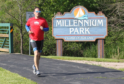 Candace H. Johnson-For Shaw Media Sean Hilliard, of Elburn runs past the Millennium Park sign on his way back to the finish line at Lakefront Park during the Fox Lake Duathlon in Fox Lake. The course included a 1-mile run, biking 12.5 miles and then finishing up with a 3.1 miles run. (6/2/19)