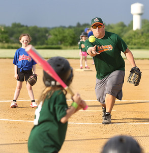 Candace H. Johnson-For Shaw Media Hurricanes Steve Hinze, coach, delivers a pitch to Katie Velez, 7, against the Jayhawks during the Grayslake Park District's in-house softball league game for grades 1st-3rd at Alleghany Park in Grayslake.  (6/11/19)
