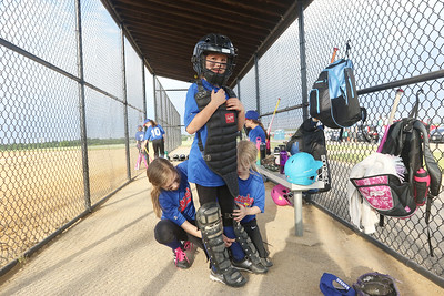 Candace H. Johnson-For Shaw Media Jayhawks Lily Johnston gets some help putting on her catcher's gear from Makayla Rowe and Riley Menning before going out on the field as her team plays the Hurricanes during the Grayslake Park District's in-house softball league game for grades 1st-3rd at Alleghany Park in Grayslake.  (6/11/19)