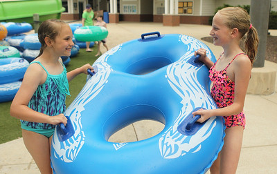 Candace H. Johnson-For Shaw Media Sydney Albert and Michaela Wilkinson, both 9, of Gurnee carry their inflatable tube to the tube slide at the Hunt Club Park Aquatic Center in Gurnee. (6/8/19)
