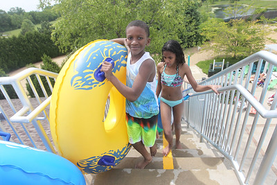 Candace H. Johnson-For Shaw Media Isahia Lulias, 12, of Lindenhurst and Deyanna Campbell, 11, of North Chicago make their way up the stairs to the tube slide at the Hunt Club Park Aquatic Center in Gurnee. (6/8/19)