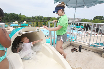 Candace H. Johnson-For Shaw Media Elushu Martynenko, 8, of Round Lake Beach waves to Ashley Thomas, 16, of Gurnee, pool attendant, as he starts to go down the tube slide at the Hunt Club Park Aquatic Center in Gurnee. (6/8/19)