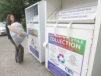 Candace H. Johnson-For Shaw Media Victoria Laurinaviciute, 25, of Grayslake puts a bag of clothes to be recycled in one of the Clothing & Textile Collection SWALCO bins at the Grayslake Recycling Center on Berry Avenue in Grayslake. (6/12/19)