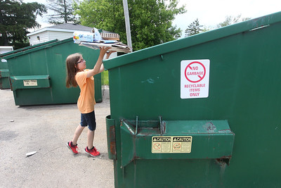 Candace H. Johnson-For Shaw Media Penny Springer, 8, of Grayslake puts some cardboard into a dumpster to be recycled at the Grayslake Recycling Center on Berry Avenue in Grayslake. (6/11/19)