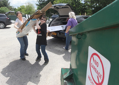 Candace H. Johnson-For Shaw Media Kirstin Springer, of Grayslake gets some help from her son, Jackson 11, taking cardboard boxes to a dumpster to be recycled at the Grayslake Recycling Center on Berry Avenue in Grayslake. (6/11/19)