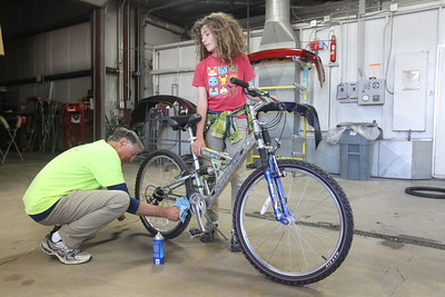 Candace H. Johnson-For Shaw Media Arthur Paton, of Round Lake helps Jack Lonigro, 13, of Wauconda fix up the donated bike he will take home during the Round Lake Area Bicycle Club's Build-A-Bike Workshop for teenagers at Collision Solution in Hainesville.  (6/13/19)