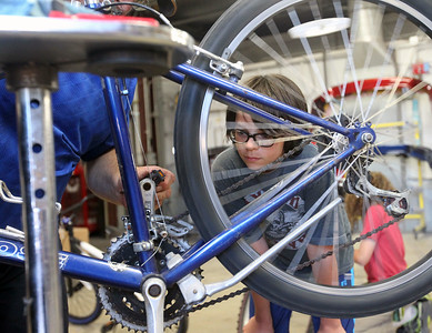 Candace H. Johnson-For Shaw Media Payton Reinert, of Volo (center) watches Greg Weeg, of Round Lake Beach fix the donated bike he will take home during the Round Lake Area Bicycle Club's Build-A-Bike Workshop for teenagers at Collision Solution in Hainesville.  (6/13/19)