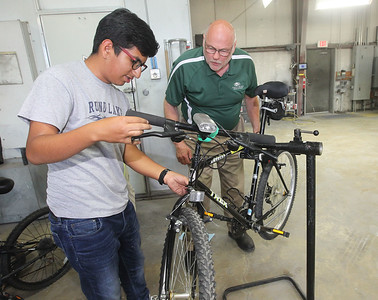Candace H. Johnson-For Shaw Media Saul Torres, 15, of Round Lake gets some help from Hal Davis, of Round Lake Beach, owner of Collision Solution, adjusting the speed controls on a donated bike he picked out and will take home during the Round Lake Area Bicycle Club's Build-A-Bike Workshop for teenagers at Collision Solution in Hainesville.  (6/13/19)
