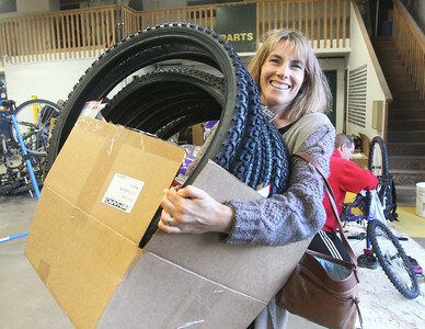 Candace H. Johnson-For Shaw Media Coordinator Anastassia Strine, of Round Lake brings in a box of bicycle tires from B & G Cyclery to use on donated bikes in need of repair during the Round Lake Area Bicycle Club's Build-A-Bike Workshop for teenagers at Collision Solution in Hainesville.  (6/13/19)