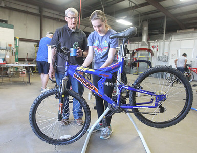 Candace H. Johnson-For Shaw Media Bob Hager of Johnsburg, president of B&G Cyclery of Round Lake Beach, helps Ava Schrank, 14, of Ingleside clean and grease the gear chain of the donated bike she is fixing to take home during the Round Lake Area Bicycle Club's Build-A-Bike Workshop for teenagers at Collision Solution in Hainesville.  (6/13/19)