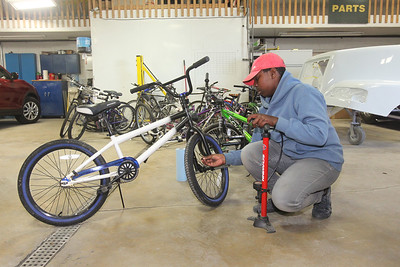 Candace H. Johnson-For Shaw Media Jacobe Smith, 14, of Ingleside fills us his bike tires with air for the donated bike he fixed and will take home during the Round Lake Area Bicycle Club's Build-A-Bike Workshop for teenagers at Collision Solution in Hainesville.  (6/13/19)