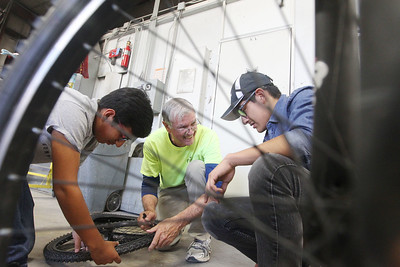 Candace H. Johnson-For Shaw Media Arthur Paton, of Round Lake (center) helps Saul Torres, 15, and Marcos Escobar, 17, both of Round Lake with fixing their donated bikes they will take home during the Round Lake Area Bicycle Club's Build-A-Bike Workshop for teenagers at Collision Solution in Hainesville.  (6/13/19)
