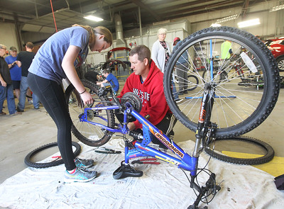 Candace H. Johnson-For Shaw Media Ava Schrank, 14, of Ingleside gets some help from her father, Tim, as she puts new tires on a donated bike she picked out to fix up and take home during the Round Lake Area Bicycle Club's Build-A-Bike Workshop for teenagers at Collision Solution in Hainesville.  (6/13/19)