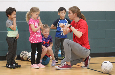 "Candace H. Johnson-For Shaw Media Coach Matthew Leyva, of Lindenhurst (on right) talks with John Garelli, 4, Kyleigh Tournas, 5, both of Volo, Gia Valenziano, 4, of Wauconda and Noah Camargo, 4, of Island Lake about how to play the game, ""Steal the Bacon,"" using a soccer ball during 5 Star Pee Wee Soccer at the Wauconda Park District Community Center. (6/16/19)"