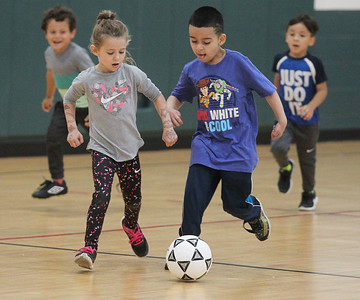 "Candace H. Johnson-For Shaw Media Sarah Goodall, 5, of Port Barrington and Christian Hermosillo, 6, of Lakemoor battle for control as they play a soccer game called, ""Steal the Bacon,"" during 5 Star Pee Wee Soccer for 4-6 year-olds at the Wauconda Park District Community Center. (6/16/19)"