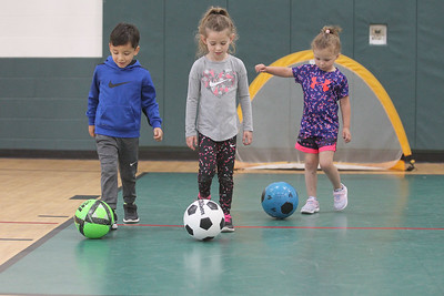 "Candace H. Johnson-For Shaw Media Noah Camargo, 4, of Island Lake, Sarah Goodall, 5, of Port Barrington and Gia Valenziano, 4, of Wauconda play the game, ""Red Light, Green Light,""  as they learn ball control and dribbling during 5 Star Pee Wee Soccer for 4-6 year-olds at the Wauconda Park District Community Center. (6/16/19)"