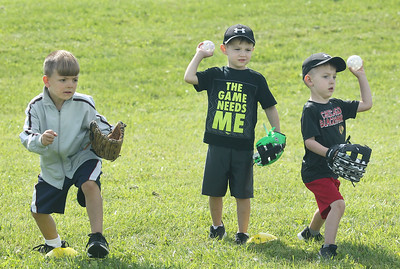 Candace H. Johnson-For Shaw Media Harry Dean, 6, of Antioch, Bryden Schaffer, 4, of Antioch and his twin brother, Caleb, work on their form and follow through during the Antioch Parks and Recreation Hot Shots Sports T-Ball at Trevor Creek Park in Antioch. (6/22/19)