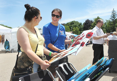 Candace H. Johnson-For Shaw Media Ashley Laycox, of Round Lake Beach and Jasmine Sandora, of Johnsburg look at artwork for sale by the Perkowitz Art Studio during the Grayslake Arts Festival in downtown Grayslake. (6/22/19)