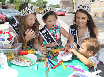 Candace H. Johnson-For Shaw Media Brianna Restrepo, 11, Vivian Camp, 7, and Makayla Steinberg, 15, newly crowned Grayslake queens help Callen Baldauf, 2, of Gurnee with a craft in the Grayslake Arts Alliance booth during the Grayslake Arts Festival in downtown Grayslake. (6/22/19)