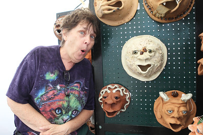 Candace H. Johnson-For Shaw Media Therese Kobel, of Grayslake has some fun showing off her unique garden art for sale in her booth during the Grayslake Arts Festival in downtown Grayslake. (6/22/19)