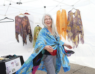 Candace H. Johnson-For Shaw Media Sherri Wistrom, of Kenosha, Wis., fiber artist, twirls as she shows off one of the handmade shawls she was selling during the Grayslake Arts Festival in downtown Grayslake. (6/22/19)