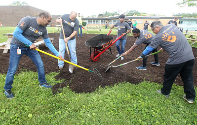 Candace H. Johnson-For Shaw Media Volunteers work on mulching a section in the back of the school to put picnic tables on for kids to eat their lunch outside during the Discover Business Technology and Volunteer Day at Gavin South Middle School in Ingleside. Over 500 volunteers from Discover Financial Services came to Gavin South to help at the event. (6/20/19)
