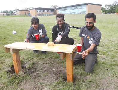 Candace H. Johnson-For Shaw Media Volunteers Lovella Chosener, of Antioch, Lillian Najabi, of Evanston and Dhruv Mehta, of Hoffman Estates work on staining a bench for an outdoor classroom during the Discover Business Technology and Volunteer Day at Gavin South Middle School in Ingleside. Over 500 volunteers from Discover Financial Services came to Gavin South to help at the event. (6/20/19)
